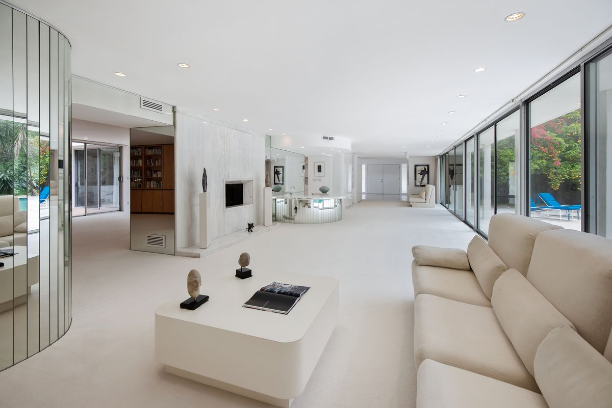 A large room with white carpet, a white sofa, and a large white coffee table. The wall on the right side is all glass and steel.