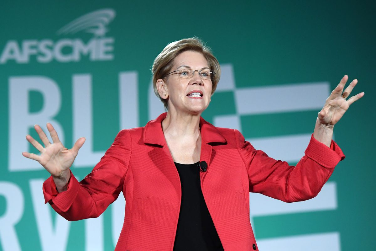 Democratic Presidential Candidates Elizabeth Warren giving a speech with her hands raised as she talks.