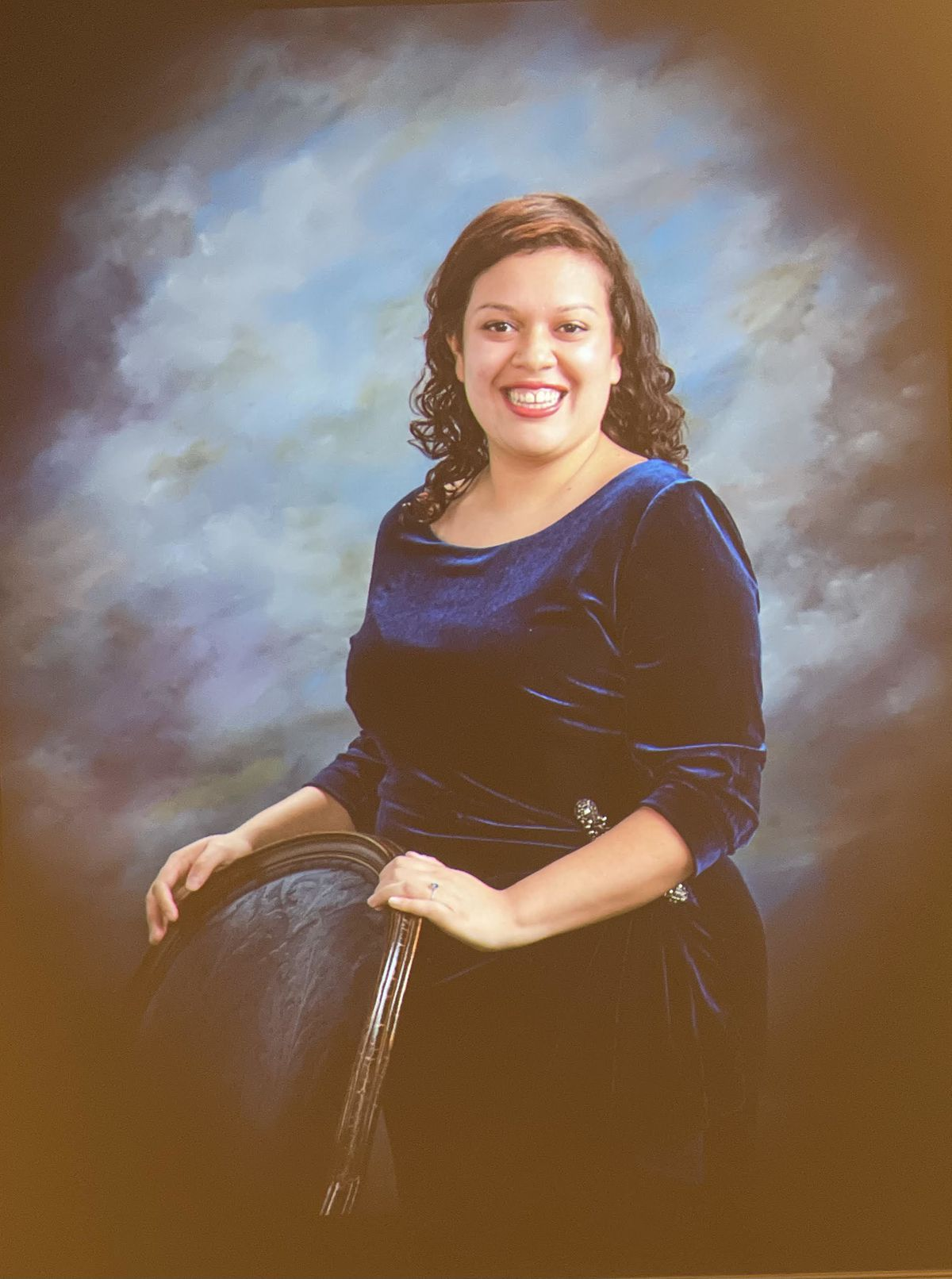 A formal portrait of a woman wearing a dark blue dress holding the back of a chair. She is seen smiling at the camera.
