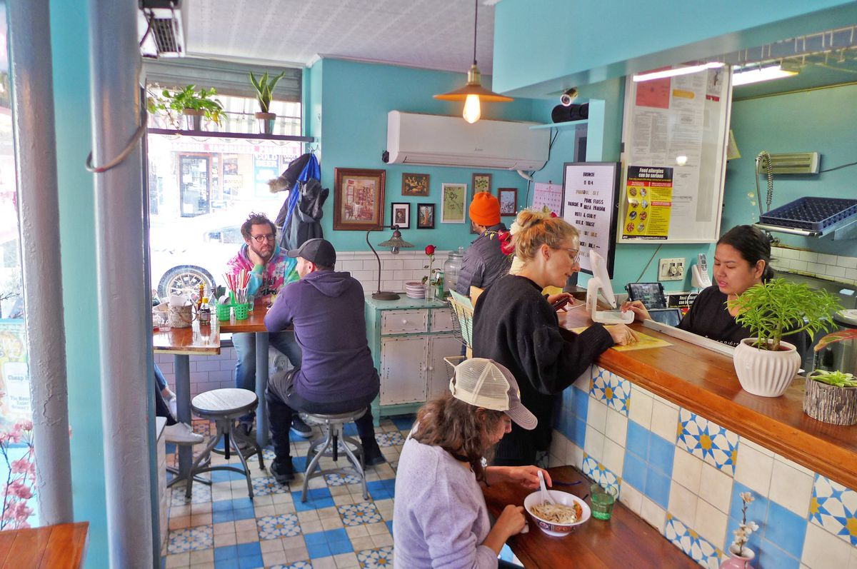 Four diners jammed in at tables and counters, while a counter person confers with a customer.