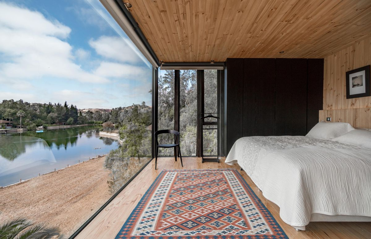 A bedroom with a window that opens out onto lakefront.