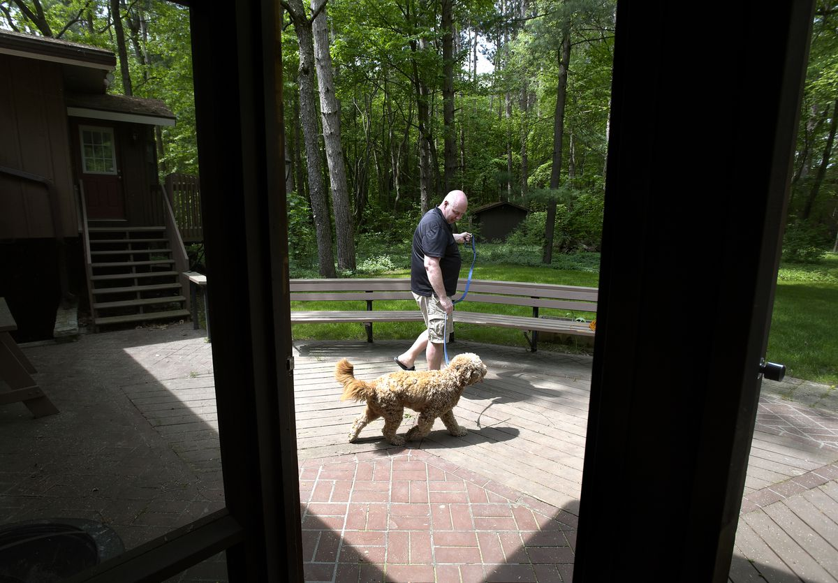 Boyd Chappell, a hospital executive, is pictured at his family's home in Midland, Michigan, with Jack, one of the family's dogs, on Friday May 21, 2021. Chappell was a longtime Republican who now considers himself politically homeless.