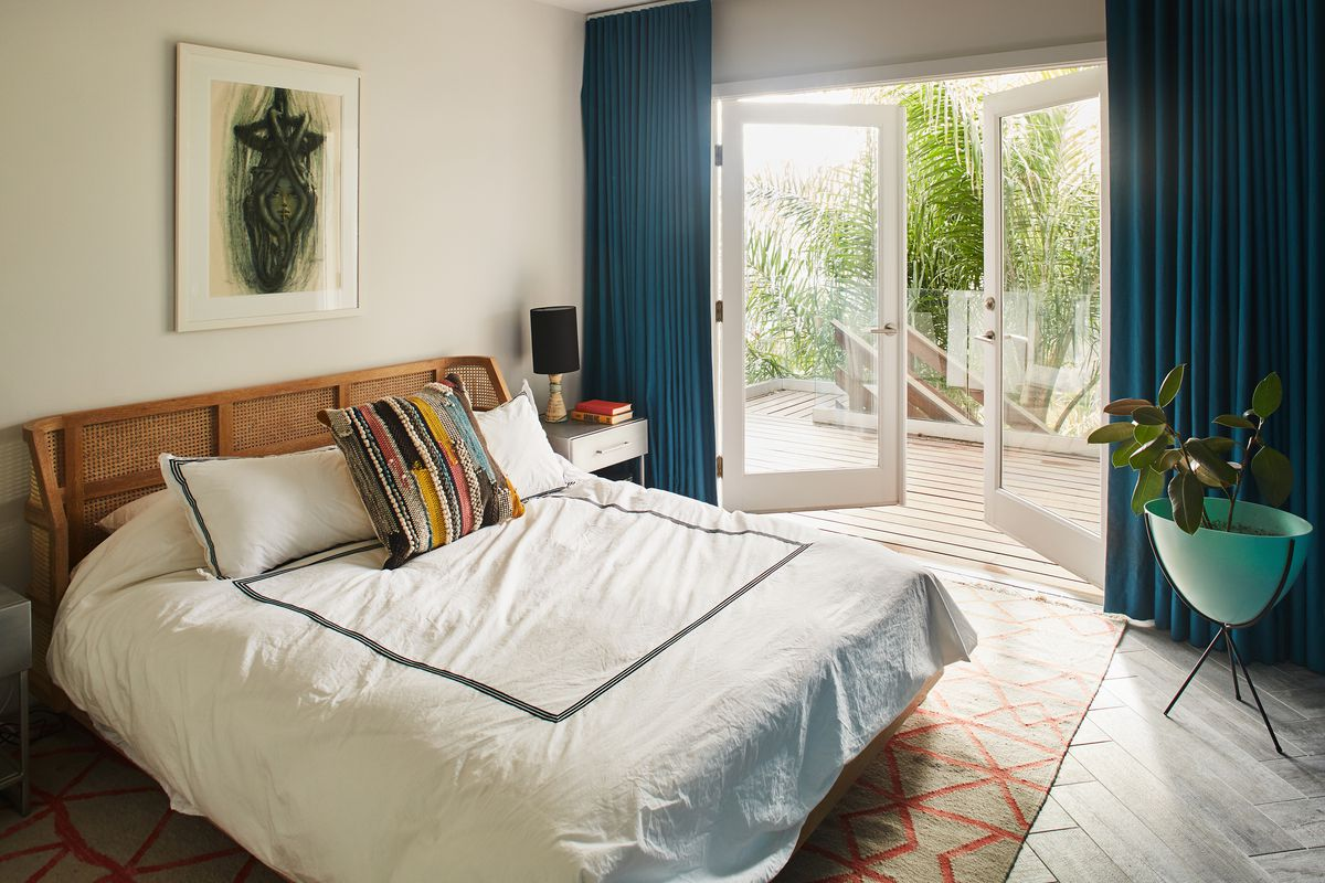 A bedroom with white bedding, and french doors open to the outside, lined by dark blue curtains.