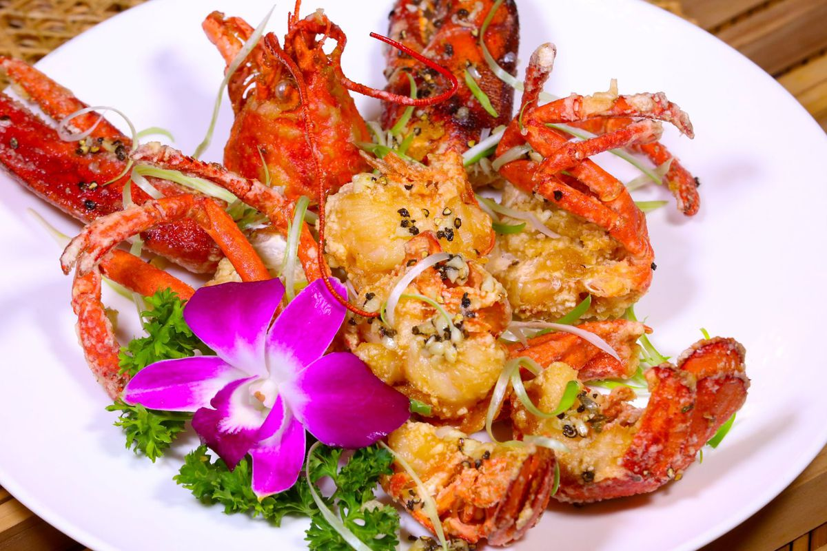 a bowl of shrimp and seafood garnished with a purple orchid flower
