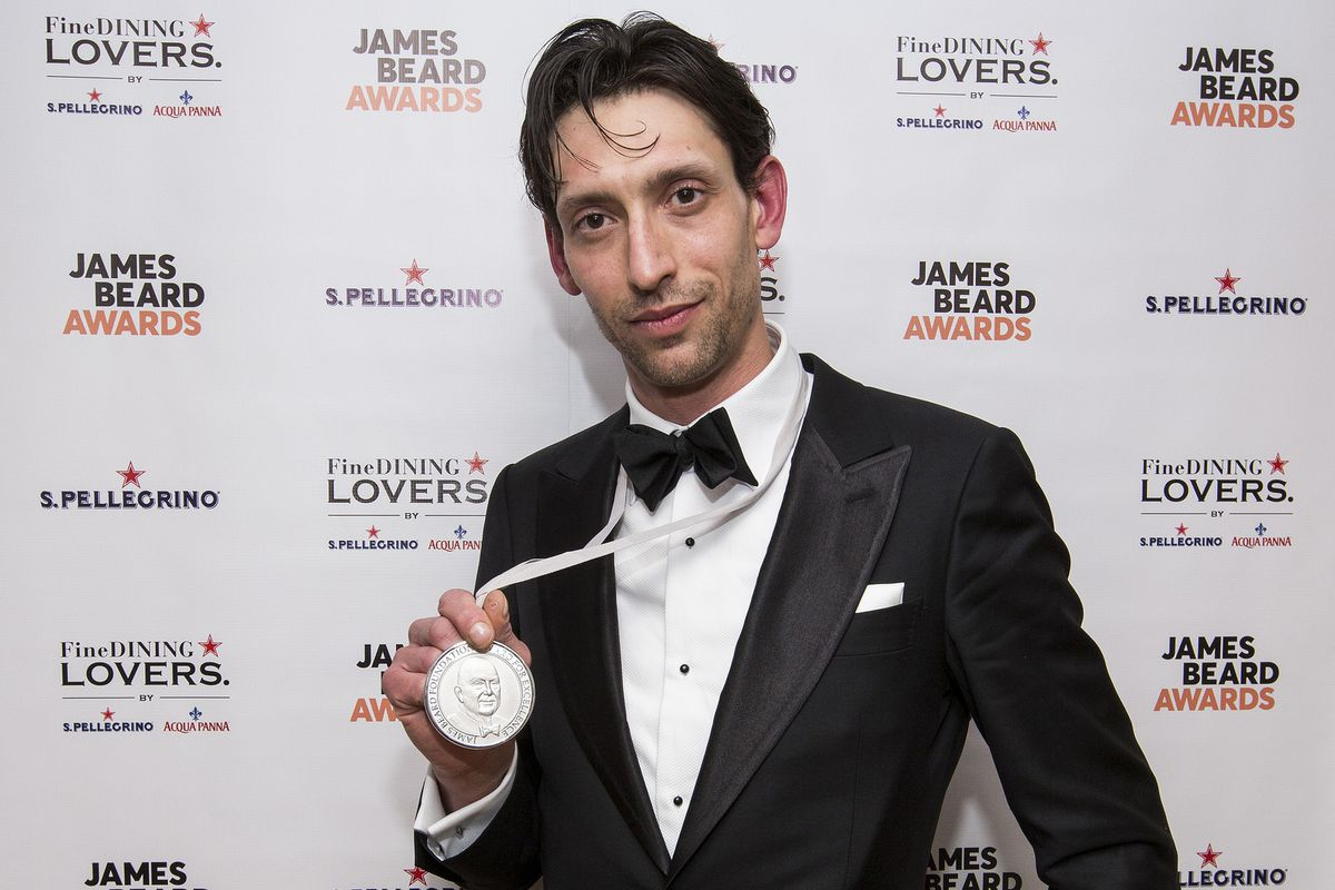 A man dressed in a black tuxedo holding a silver medal worn around his neck.