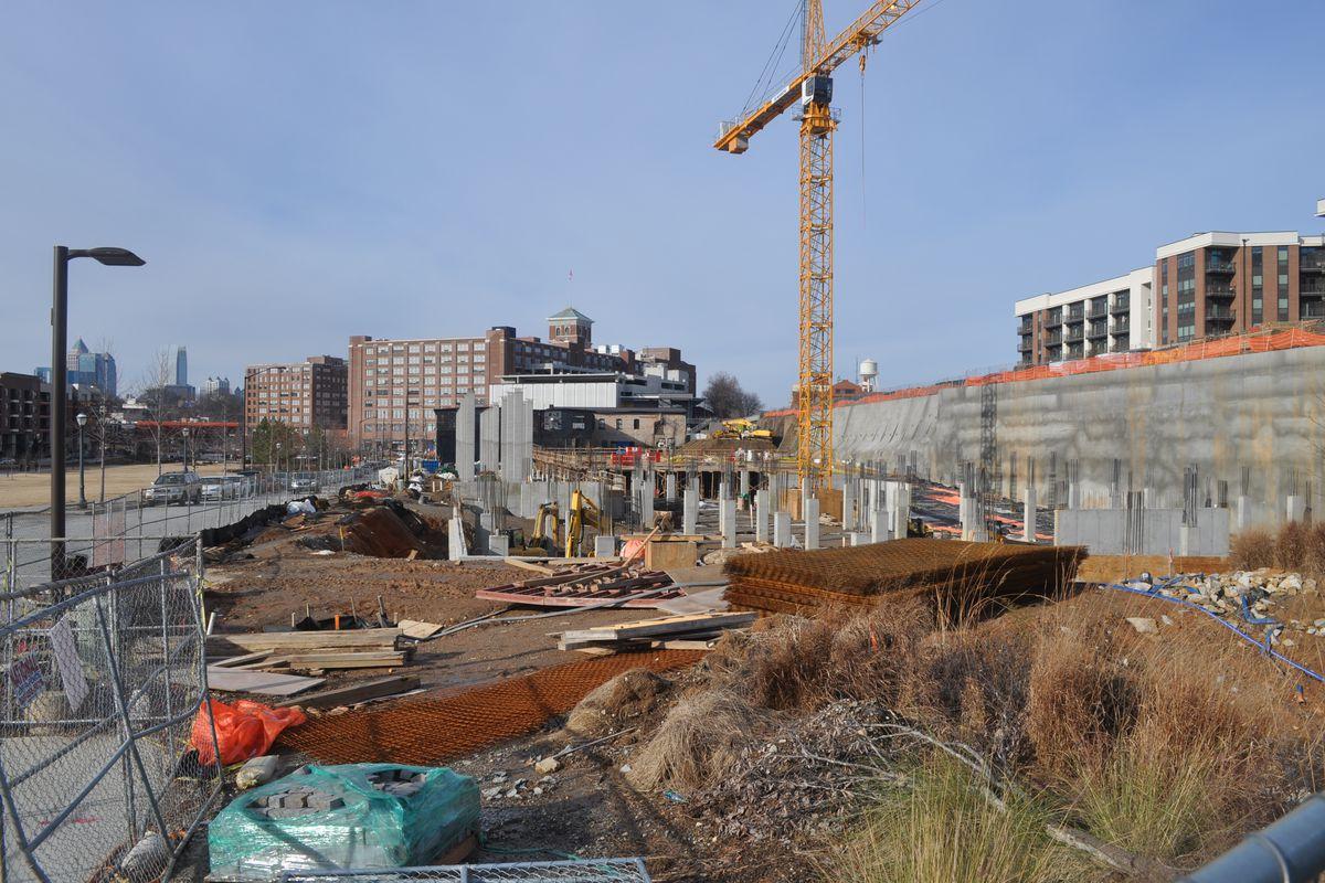 A crane stands above a construction site where concrete columns are rising.