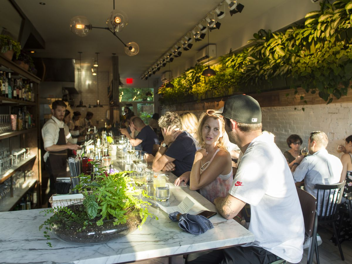 Patrons sit at the bar at Olmsted surrounded by plants