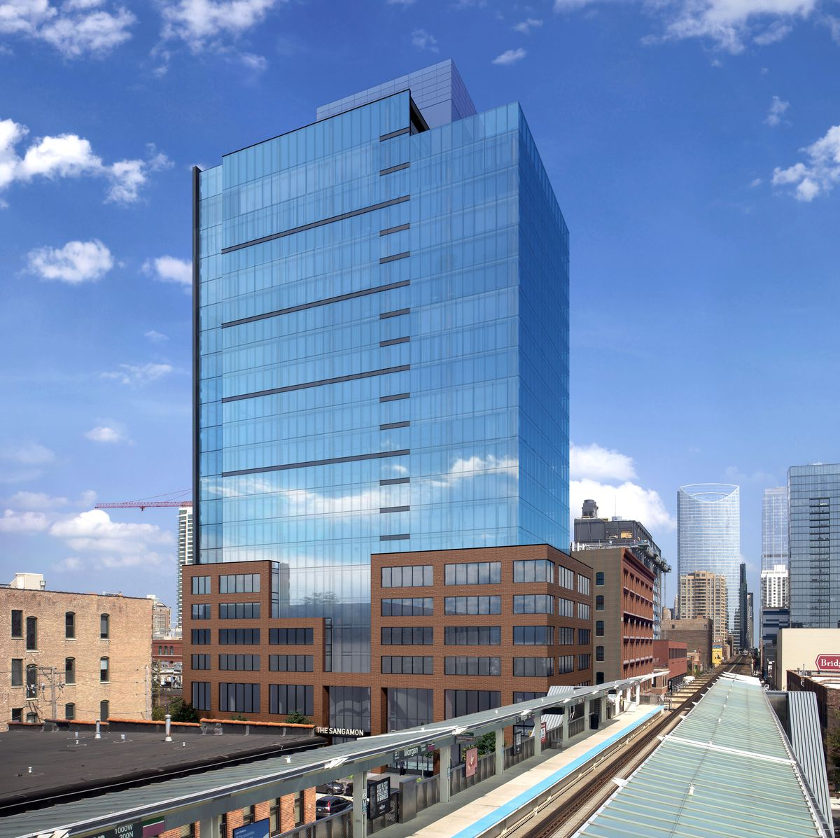 A 20-story rectangular building with a brick base. blue glass upper levels, and stepped roof rises near the Morgan CTA station. The Chicago skyline is visible beyond.