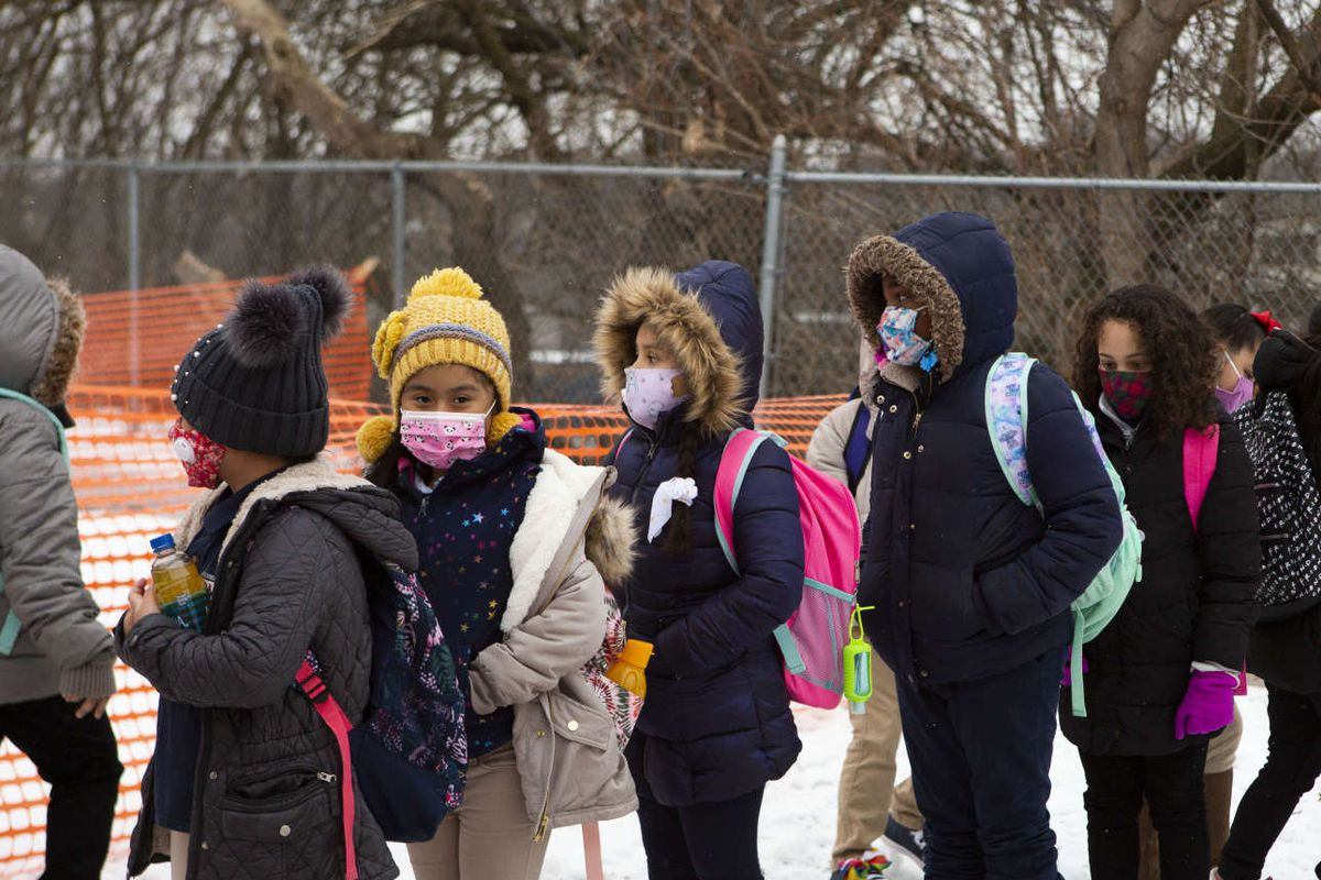 Masked students wait in line to enter a Grand Rapids school building