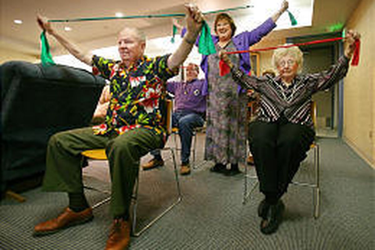 Lynette Sali, standing, leads stretching exercises for participants Bob Wecker, left, and Maxine Read.