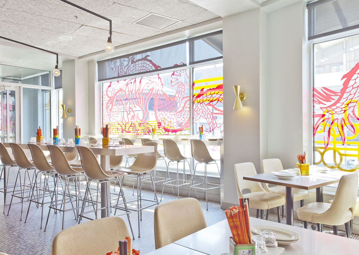A bright restaurant interior with high tan stools and decorative window art