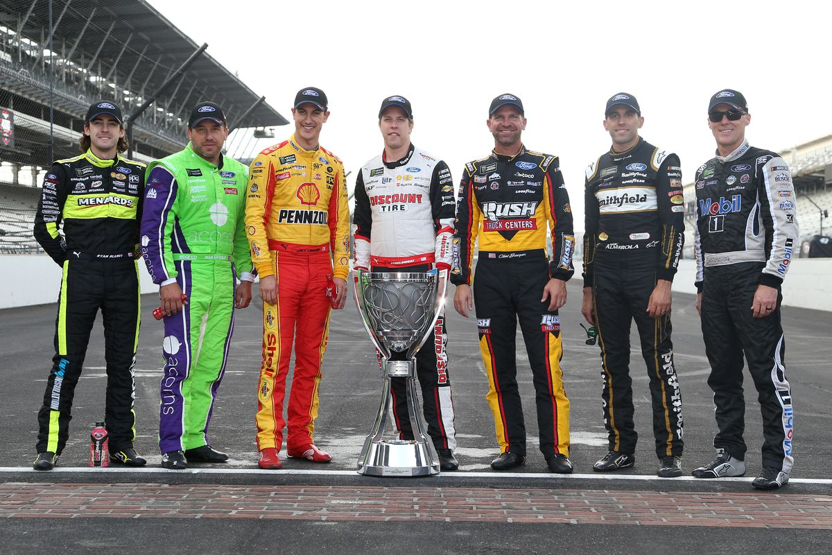 Ryan Blaney, Ryan Newman, Joey Logano, Brad Keselowski, Clint Bowyer, Aric Almirola, and Kevin Harvick, pose for a photo with the Monster Energy NASCAR Cup Series trophy to start the playoffs following the Monster Energy NASCAR Cup Series Big Machine Vodka 400 at the Brickyard at Indianapolis Motor Speedway on September 08, 2019 in Indianapolis, Indiana.