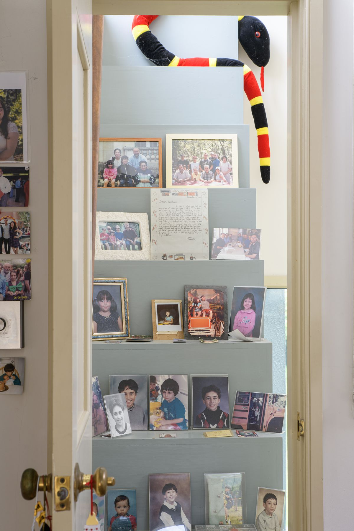A doorway that opens to a staircase. On the stairs are various framed photos, art, and letters. There is a stuffed toy snake on the top of the stairs.