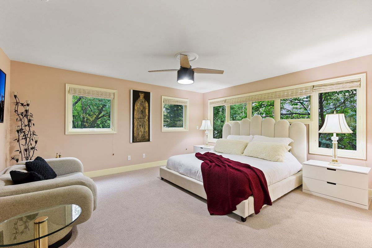 A bedroom has light peach walls, a white bed, and carpet.