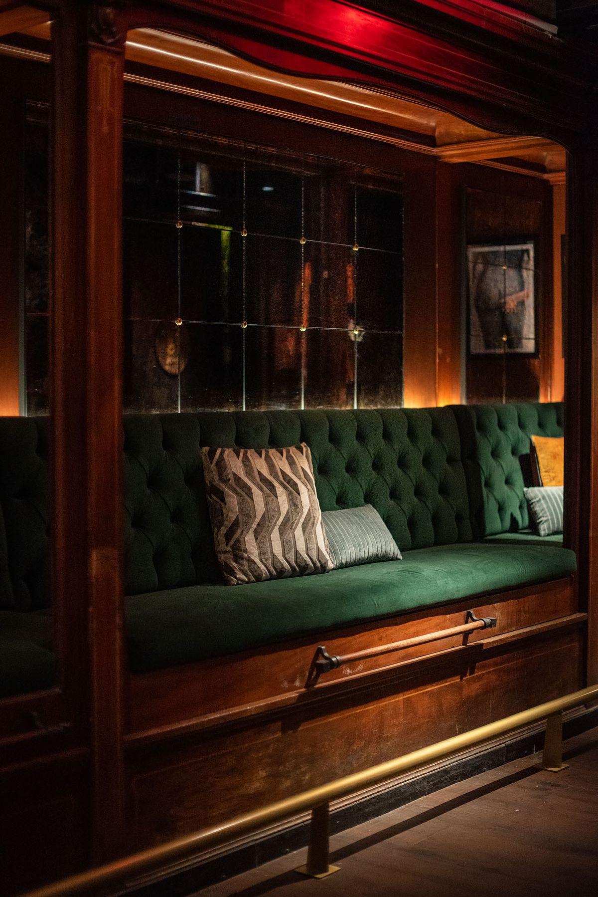 A plush dark green reading nook inside a bar.
