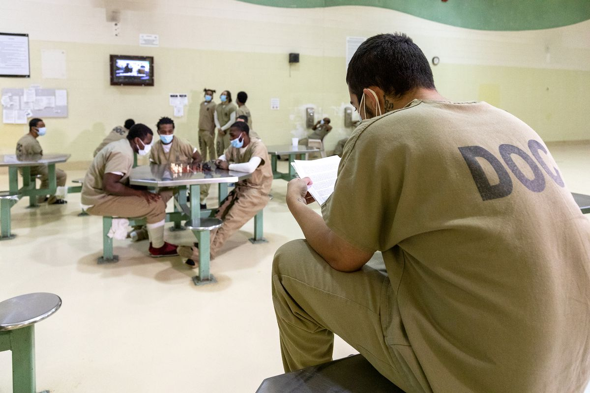 Masked detainees sit inside the Cook County Jail.