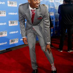 Louisville's Donovan Mitchell shows off his socks while stopping for photos on the red carpet before the start of the NBA basketball draft, Thursday, June 22, 2017, in New York. (AP Photo/Frank Franklin II)