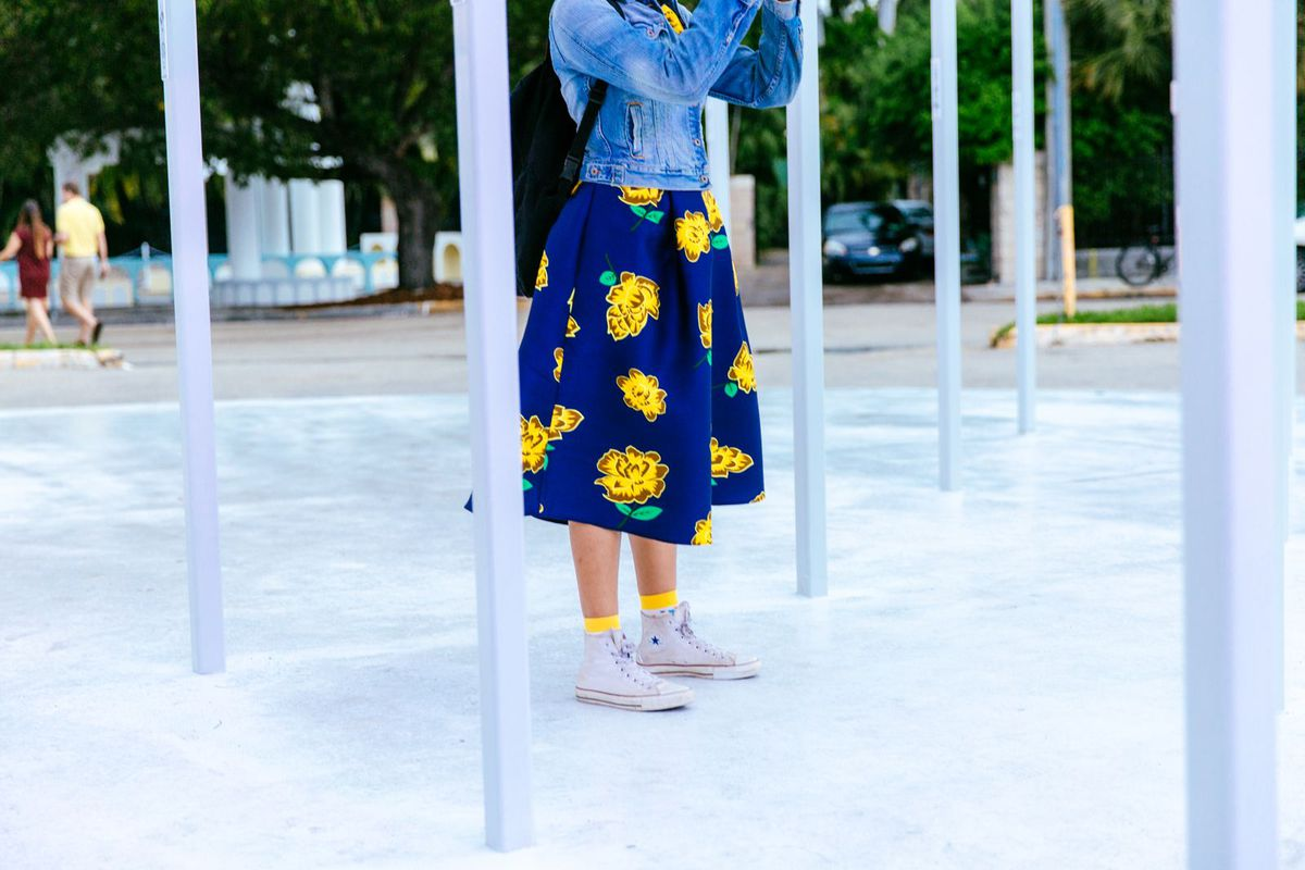 A woman in a blue and yellow dress, jean jacket, and white high-top Converse sneakers.