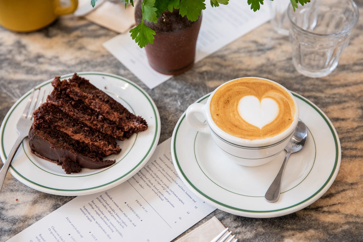 A slice of chocolate cake and a latte sit on plates at Ochre Bakery.