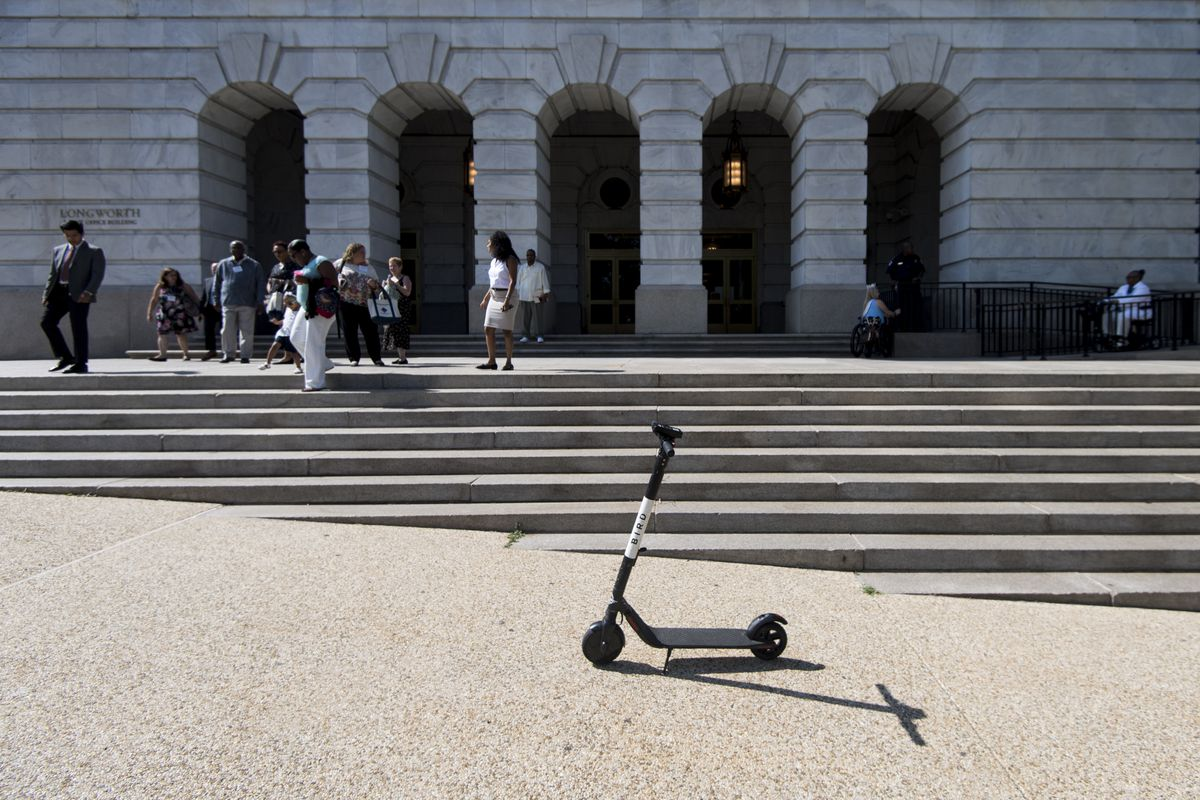 An electric scooter on a sidewalk in front of a classical building with archways.