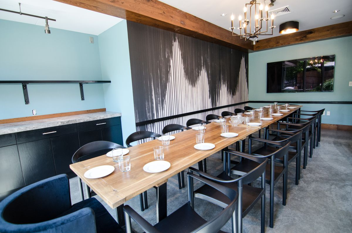 A long wooden table with about 18 chairs stretches through a private dining room at a restaurant. The walls are light blue, except for one portion, which is covered with a black-and-white-striped wallpaper. There's a television at one end of the room, and