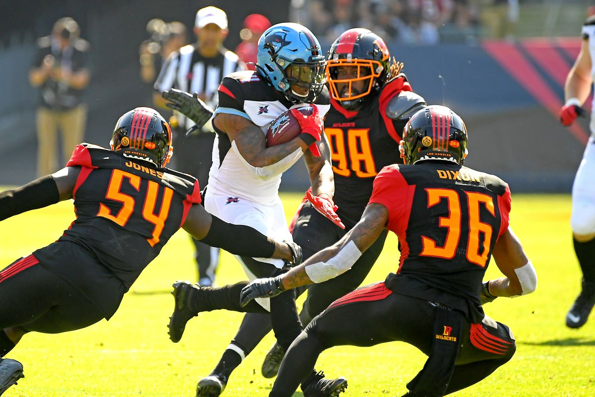 Running back Cameron Artis-Payne of the Dallas Renegades gets through the Los Angeles Wildcats defense of linebacker Taiwan Jones. defensive end Devin Taylor and safety Ahmad Dixon in the first half of the XFL game at Dignity Health Sports Park on February 16, 2020 in Carson, California.