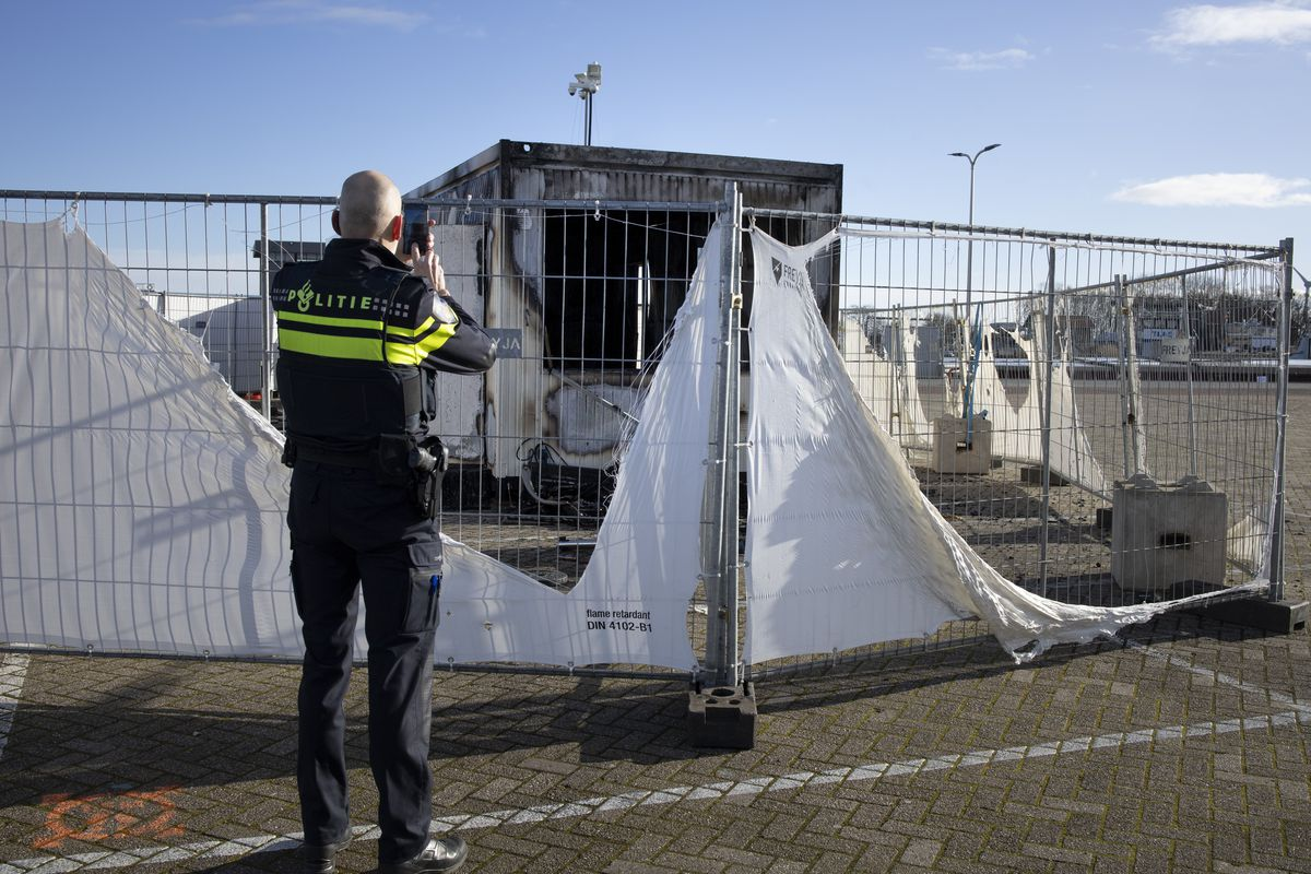 In this Jan. 24, 2021, file photo, a police officer takes pictures of a burned-out coronavirus testing facility in the fishing village of Urk in the Netherlands after it was set on fire the night before by rioting youths protesting on the first night of a nationwide curfew.