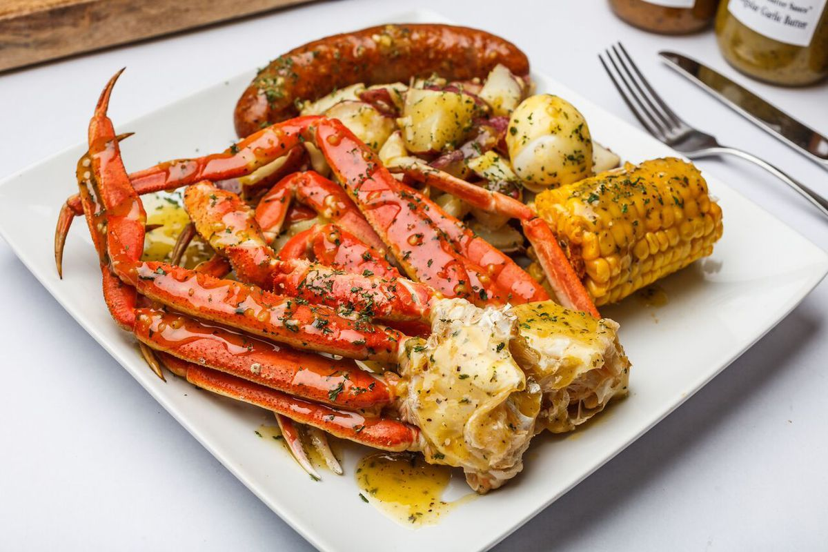 A white plate with butter-drenched king crab legs, sausage link, potatoes, and a piece of corn
