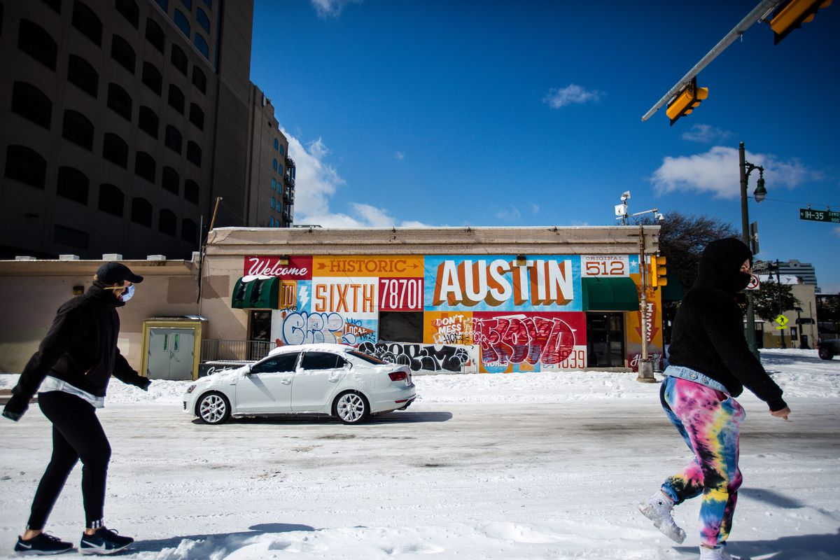 AUSTIN, TX - FEBRUARY 15: Pedestrians walk on along a snow-covered street on February 15, 2021 in Austin, Texas. Winter storm Uri has brought historic cold weather to Texas, causing traffic delays and power outages, and storms have swept across 26 states with a mix of freezing temperatures and precipitation.