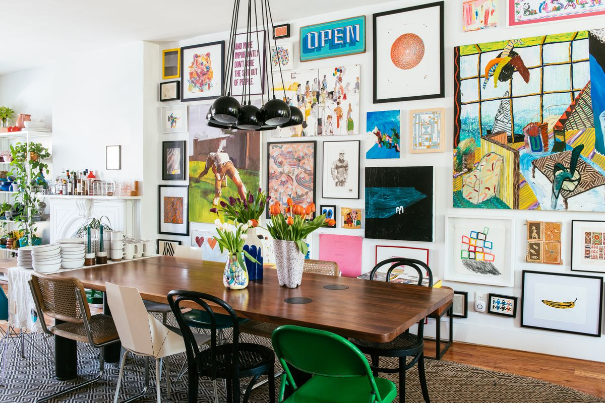 A dining room. The walls are painted white and there is a large wooden dining room table surrounded by multiple assorted chairs. There are many framed works of art hanging on one of the walls. On the table are vases with colorful flowers.