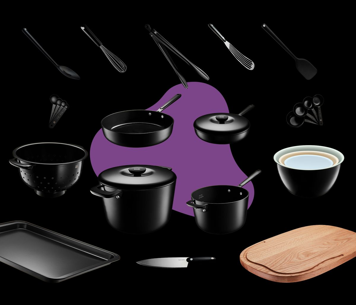 Over a dozen pieces of matte black cookware, like pots, pans and a spatula, scattered on a black background with a, abstract purple blob in the middle