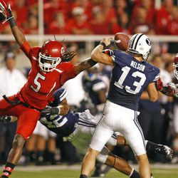 Utah Utes defensive back Mo Lee (5) knocks the ball away from Brigham Young Cougars quarterback Riley Nelson (13) in what was first called a fumble but reversed to an incomplete pass as the University of Utah and BYU play football Saturday, Sept. 15, 2012, in Salt Lake City, Utah.