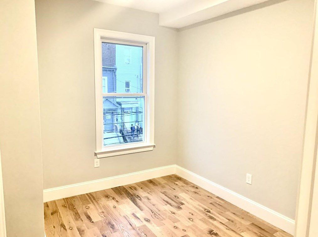 A small empty bedroom with a window.