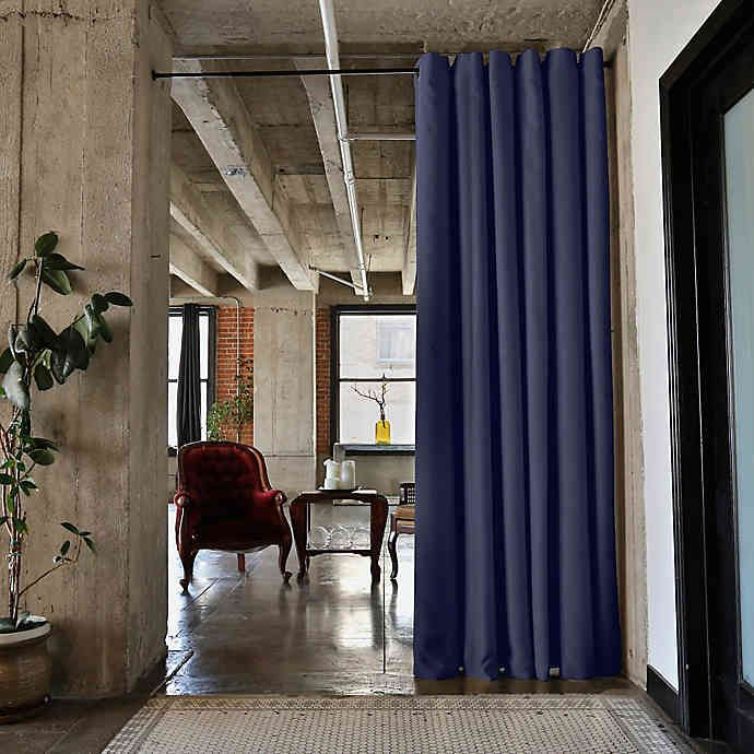 Tall blue curtains hanging over an entryway with concrete walls.