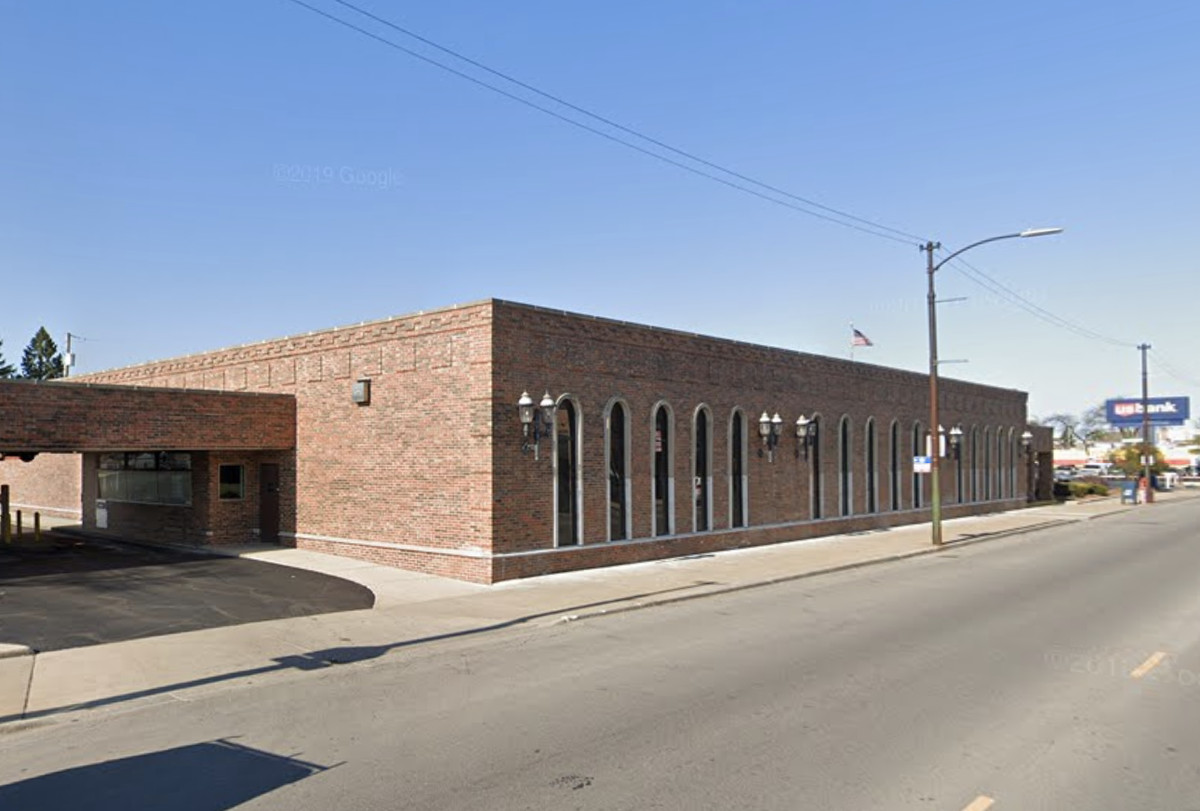 A single-story brick building on a four-lane street. The structure has vertical windows with rounded tops, exterior lamps, and covered drive-through lanes.