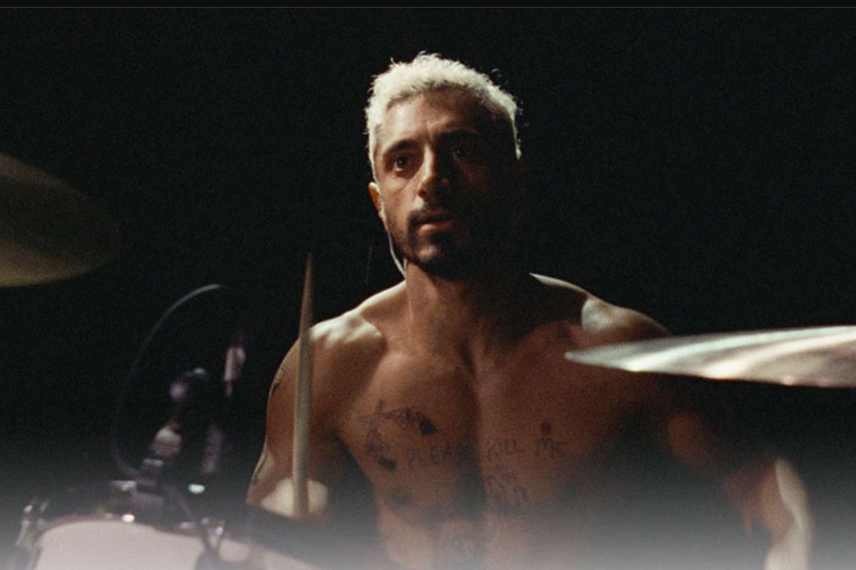 Ahmed, as Ruben, sits at a drum set shirtless against a black background.