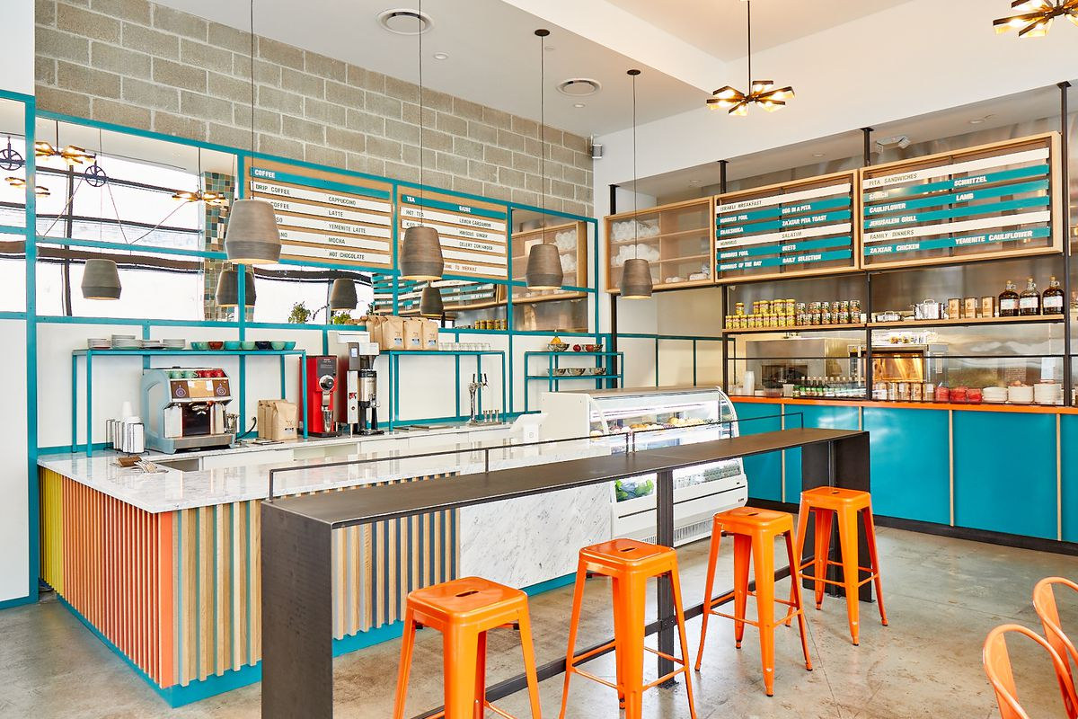 interior of brightly colored restaurant with counter and orange stools