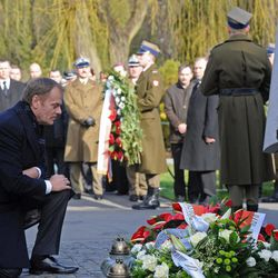 Polish Prime Minister Donald Tusk kneels in front of a memorial dedicated to the victims of a presidential plane crash during commemorations marking the second anniversary of the accident, at the Powazki cemetery in Warsaw, Poland, Tuesday, April 10, 2012. Exactly two years ago a plane with Polish President Lech Kaczynski, his wife and officials crashed in Russia, killing all on board.