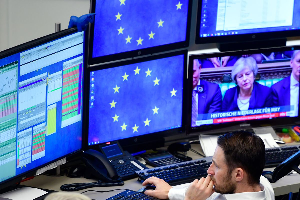 Multiple TV screens, two with the EU symbol of a circle of stars minus one star and one showing British Prime Minister Theresa May.