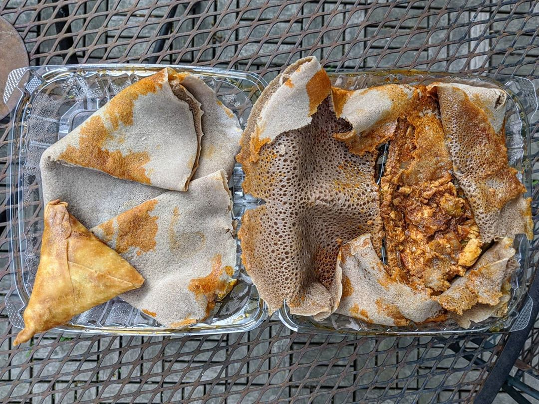 Overhead view of a takeout container of an Ethiopian chicken dish wrapped in injera, sitting on a picnic table