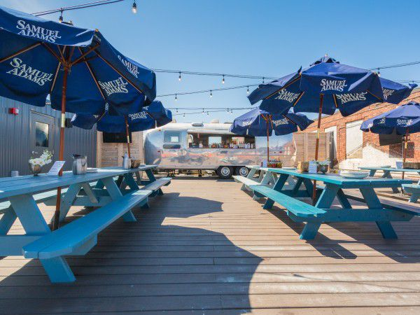 A restaurant's sunny roof deck features turquoise picnic tables and large blue umbrellas, as well as a silver Airstream bar