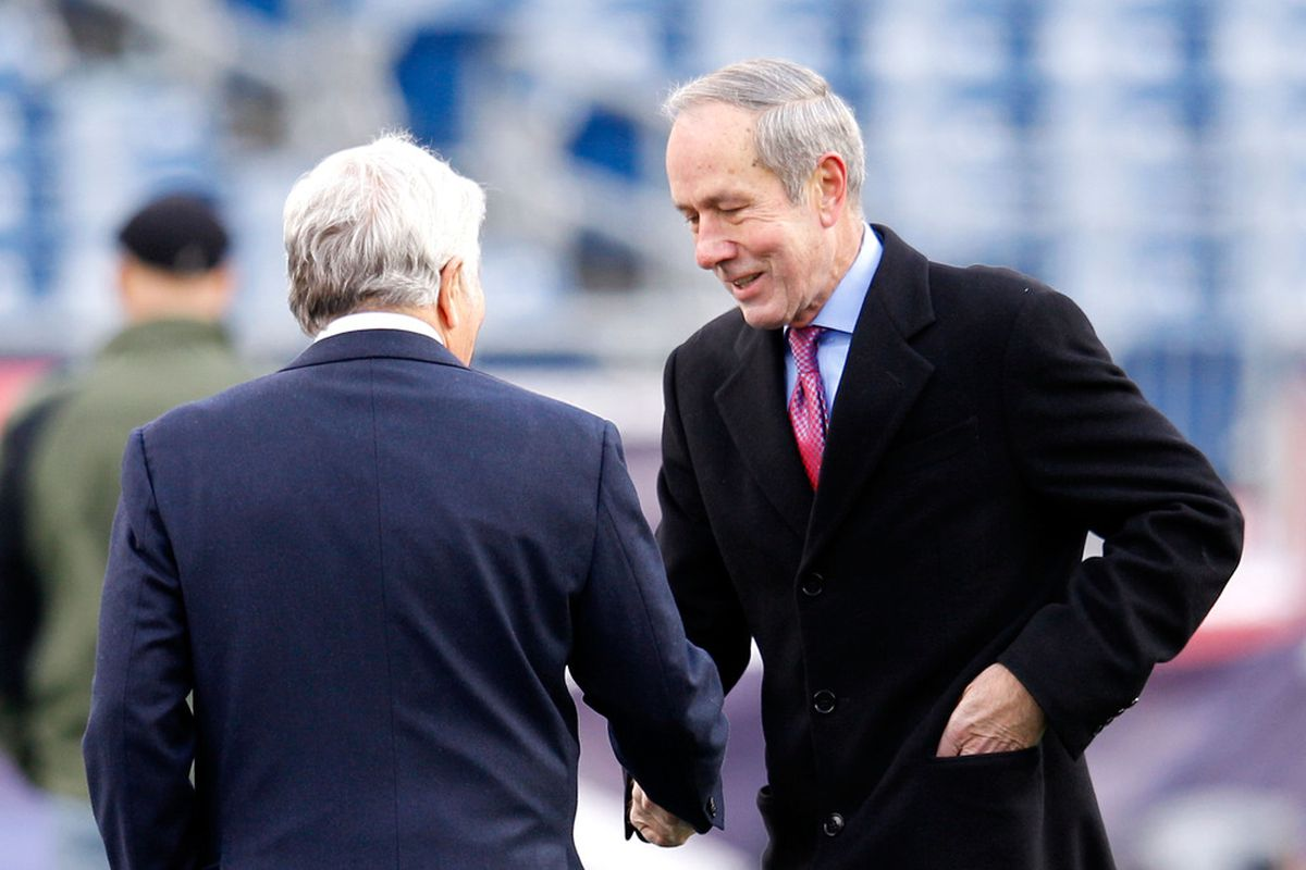 Ravens president Dick Cass (right) shakes Robert Kraft's hand. Cass helped reach a deal with D.C. radio station WBIG 100.3 to broadcast Ravens games.