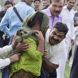In this photo taken on Saturday, Sept. 8, 2012, A Pakistani police official and a Christian volunteer escort a young Christian girl accused of blasphemy, towards a helicopter following her release from central prison on the outskirts of Rawalpindi, Pakistan. The apparent collapse of a case against a Christian girl accused of burning pages of a Quran has given a dim ray of hope to critics of Pakistan?s blasphemy laws, some of the harshest in the Muslim world.