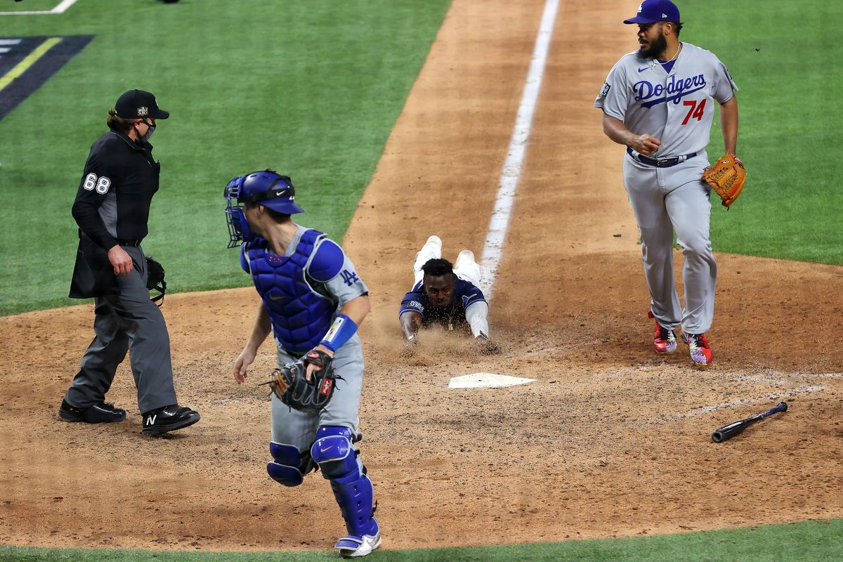 Randy Arozarena #56 of the Tampa Bay Rays slides into home plate during the ninth inning to score the game winning run to give his team the 8-7 victory against the Los Angeles Dodgers in Game Four of the 2020 MLB World Series at Globe Life Field on October 24, 2020 in Arlington, Texas.