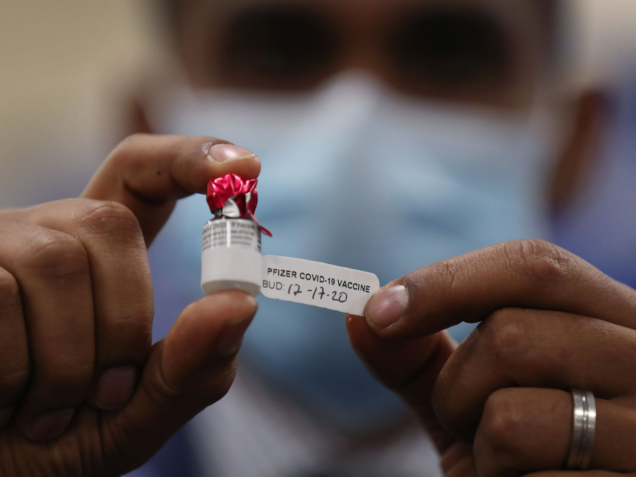 A man holding up a vaccine vial.