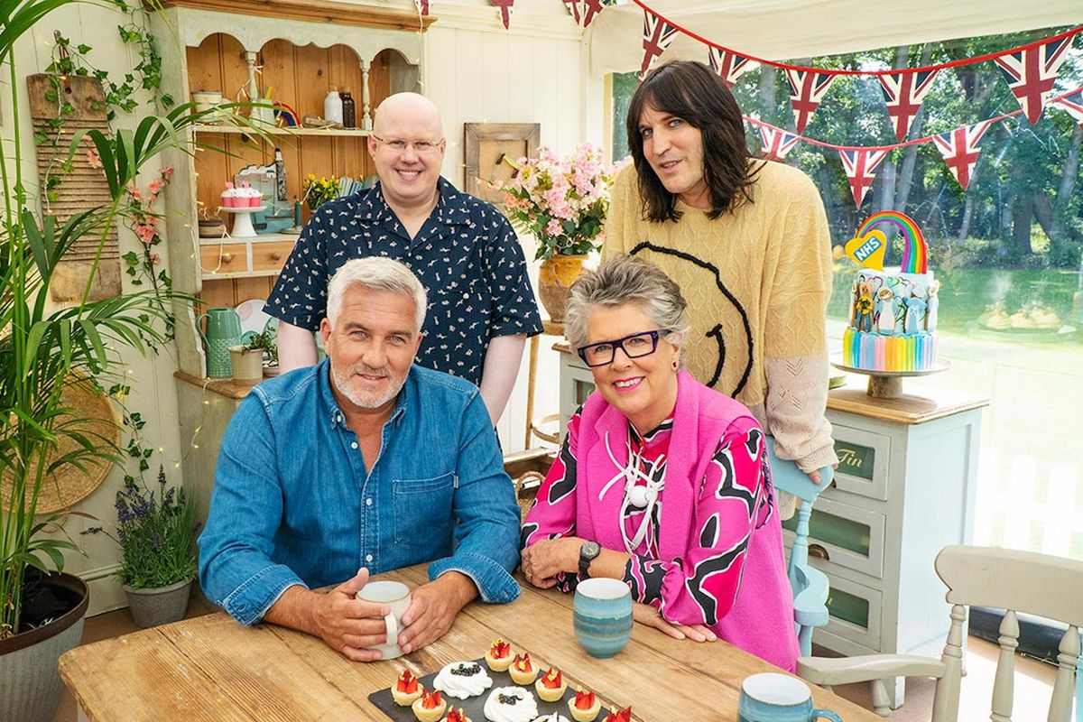"""The hosts and judges of """"The Great British Bake Off"""" gather around a light wood table with a china hutch and Union Jack bunting in the background."""