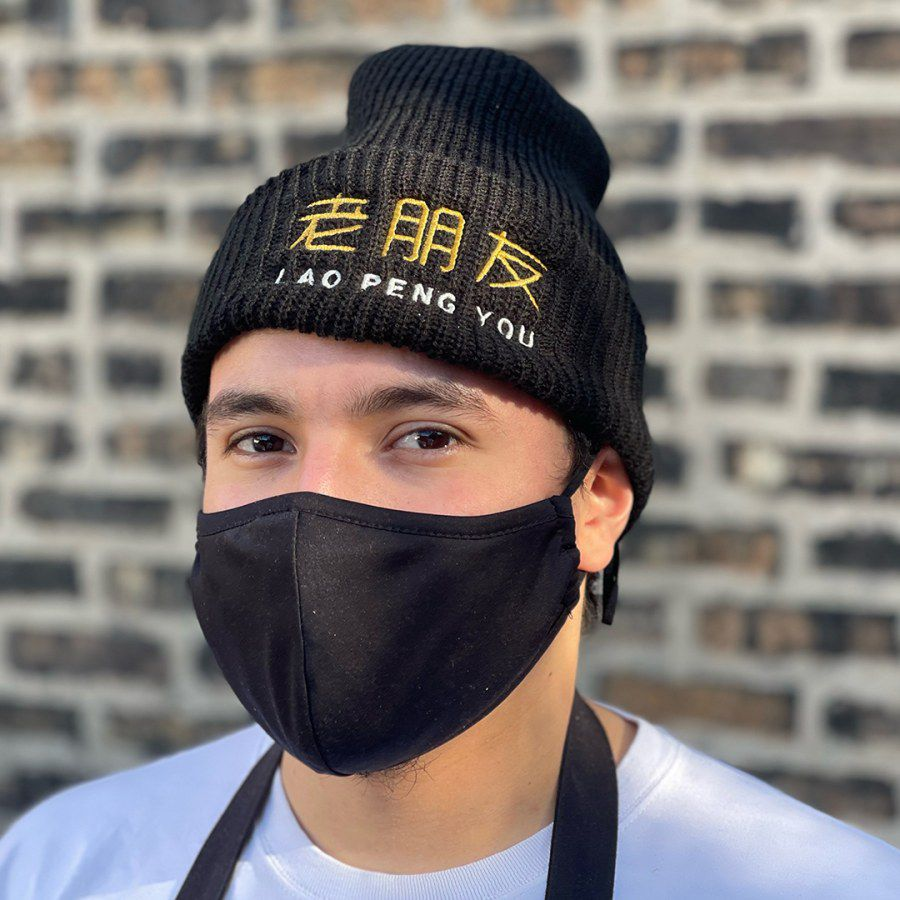 """A person wearing a black embroidered beanie that reads """"Lao Peng You"""" in English and Chinese."""