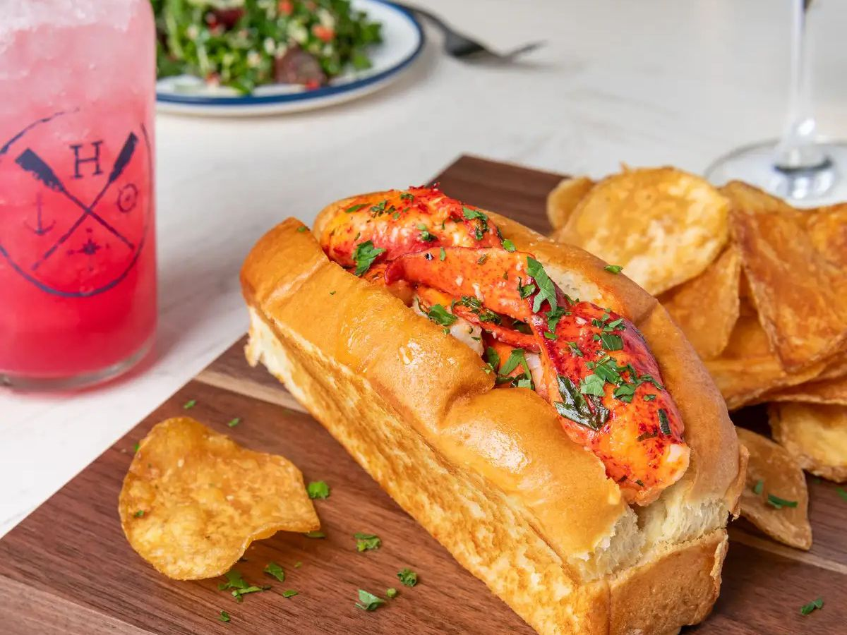 A lobster roll and chips served on a board next to a cocktail and salad.