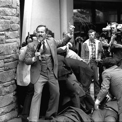 FILE - In this Monday, March 30, 1981 file photo, a Secret Service agent, automatic weapon drawn, yells orders after shots were fired at President Ronald Reagan outside a hotel in Washington. The Secret Service has been tarnished by a prostitution scandal that erupted April 13, 2012 in Colombia involving 12 Secret Service agents, officers and supervisors and 12 more enlisted military personnel ahead of President Barack Obama's visit there for the Summit of the Americas.