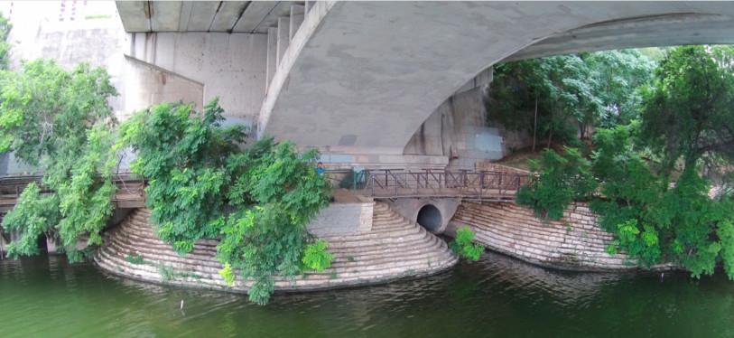 A wooden pedestrian bridge along a river under a large concrete